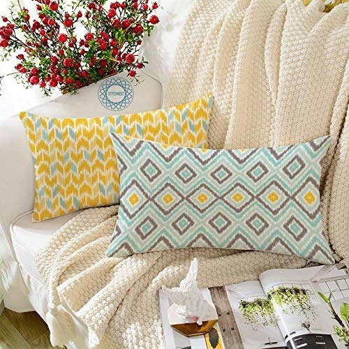 The cushions kept on a throw blanket, which is placed on a white sofa.