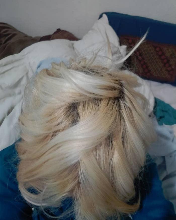 A reviewer shows their bleached blonde hair
