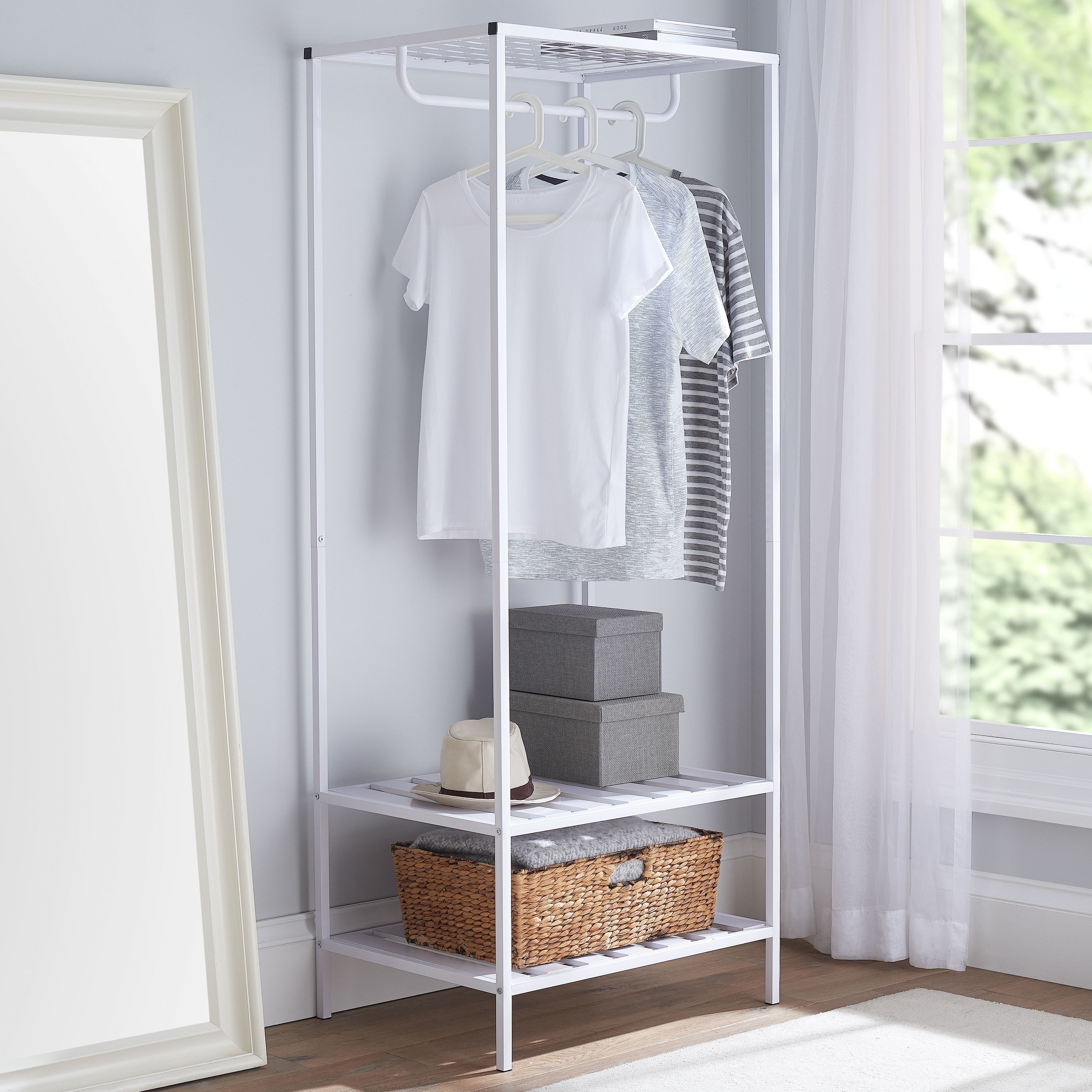 white garment rack with clothes hanging up and boxes on the bottom
