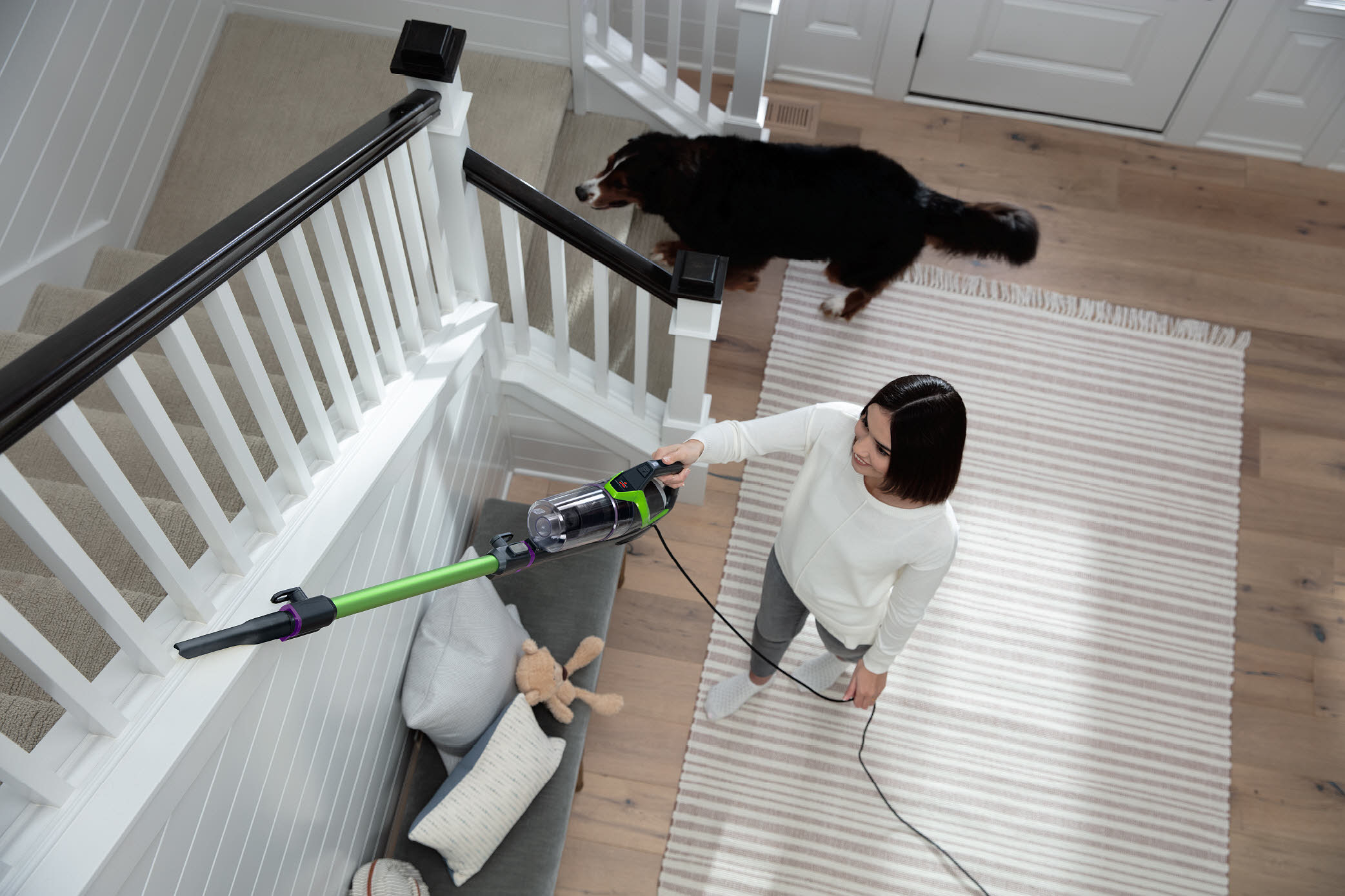 person uses bissell stick vacuum on the stairs as a dog walks behind her