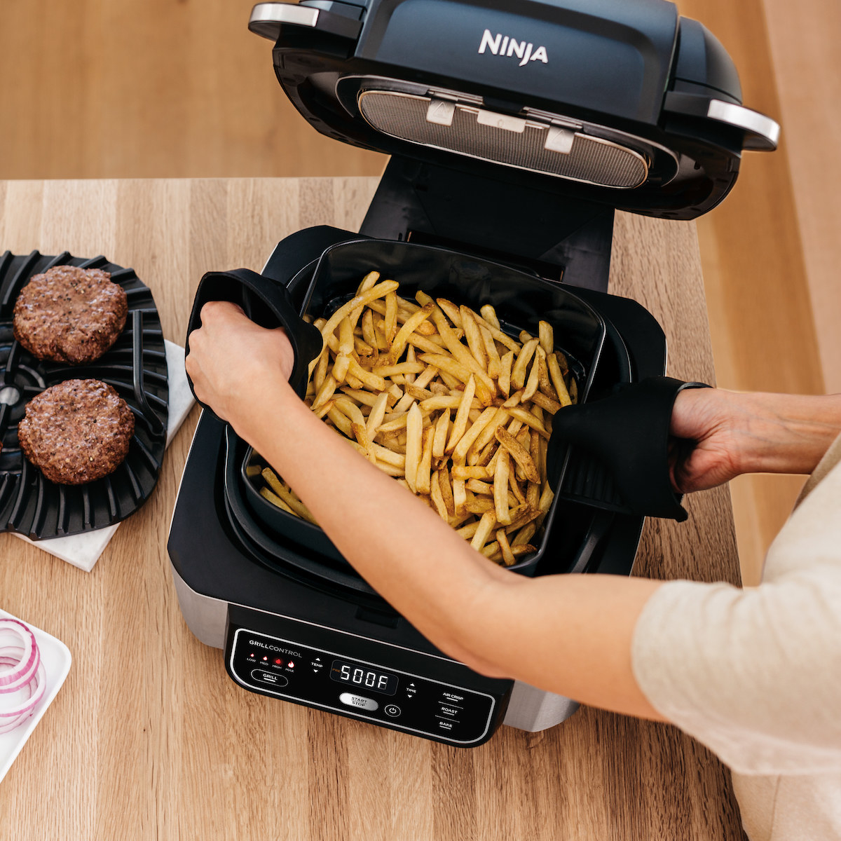 person lifting a tray of french fries out of a ninja air fryer