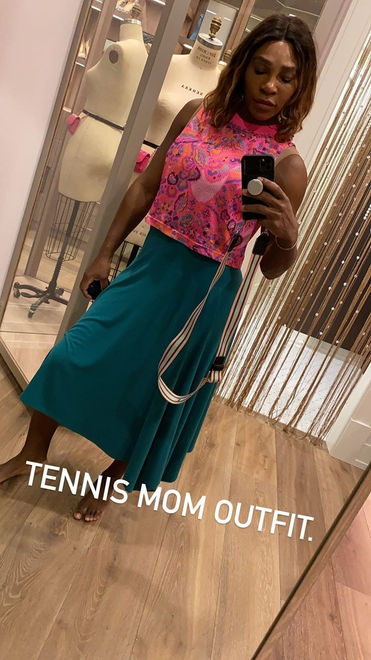 Serena Williams on Instagram Live showing off a mirror selfie of her tennis mom look — a pink tank top and green skirt