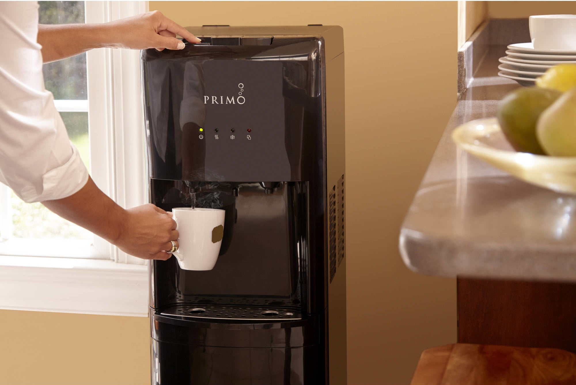 person using a primo water dispenser to get hot water for tea