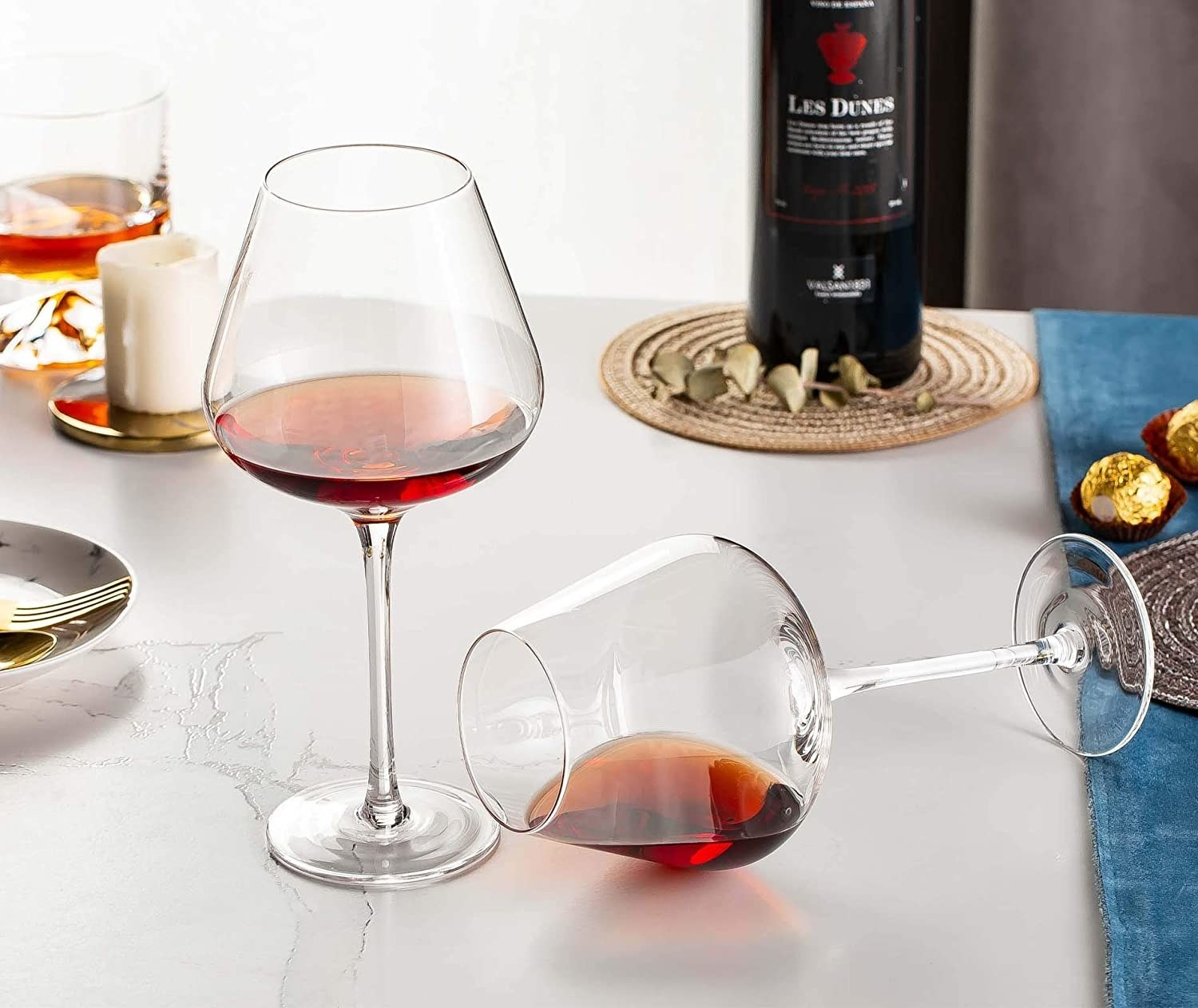 A set of two deep glass long-stemmed wine glasses with red wine