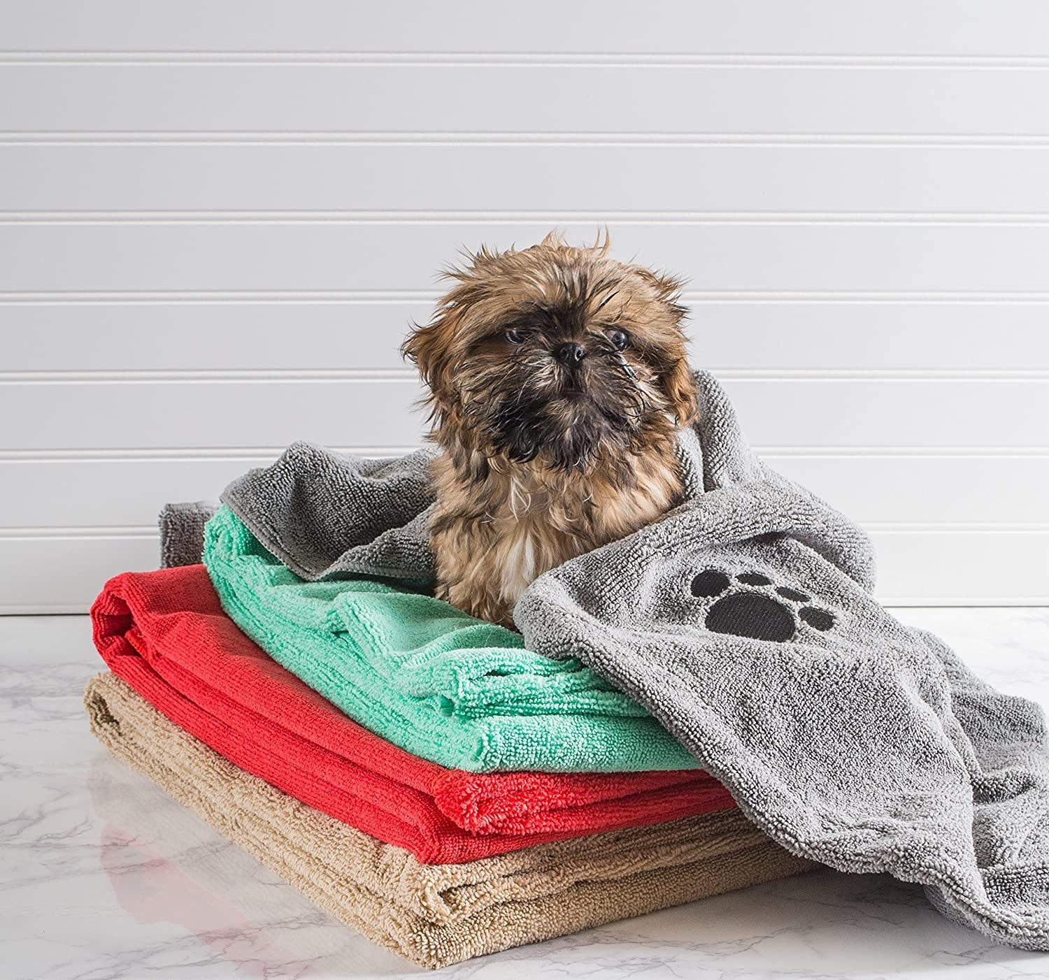 A dog wrapped in a grey towel and sitting on three towels of different colors