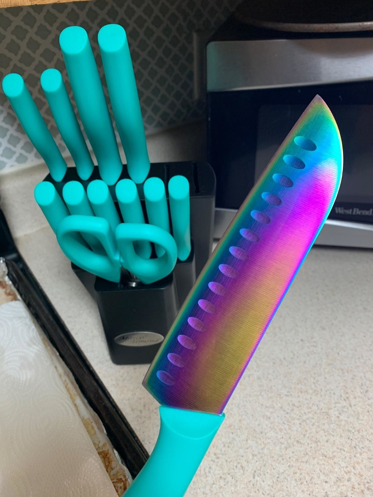 A knife with a rainbow-tinted blade and turquoise handle in front of a full set of knifes on a kitchen counter