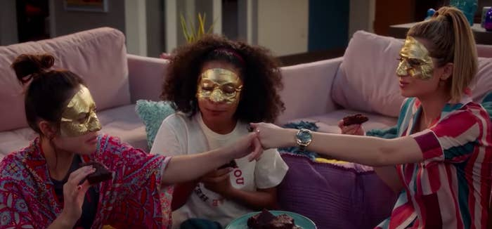 """Anna, Zoey, and Nomi from """"Grownish"""" wearing face masks and eating brownies."""