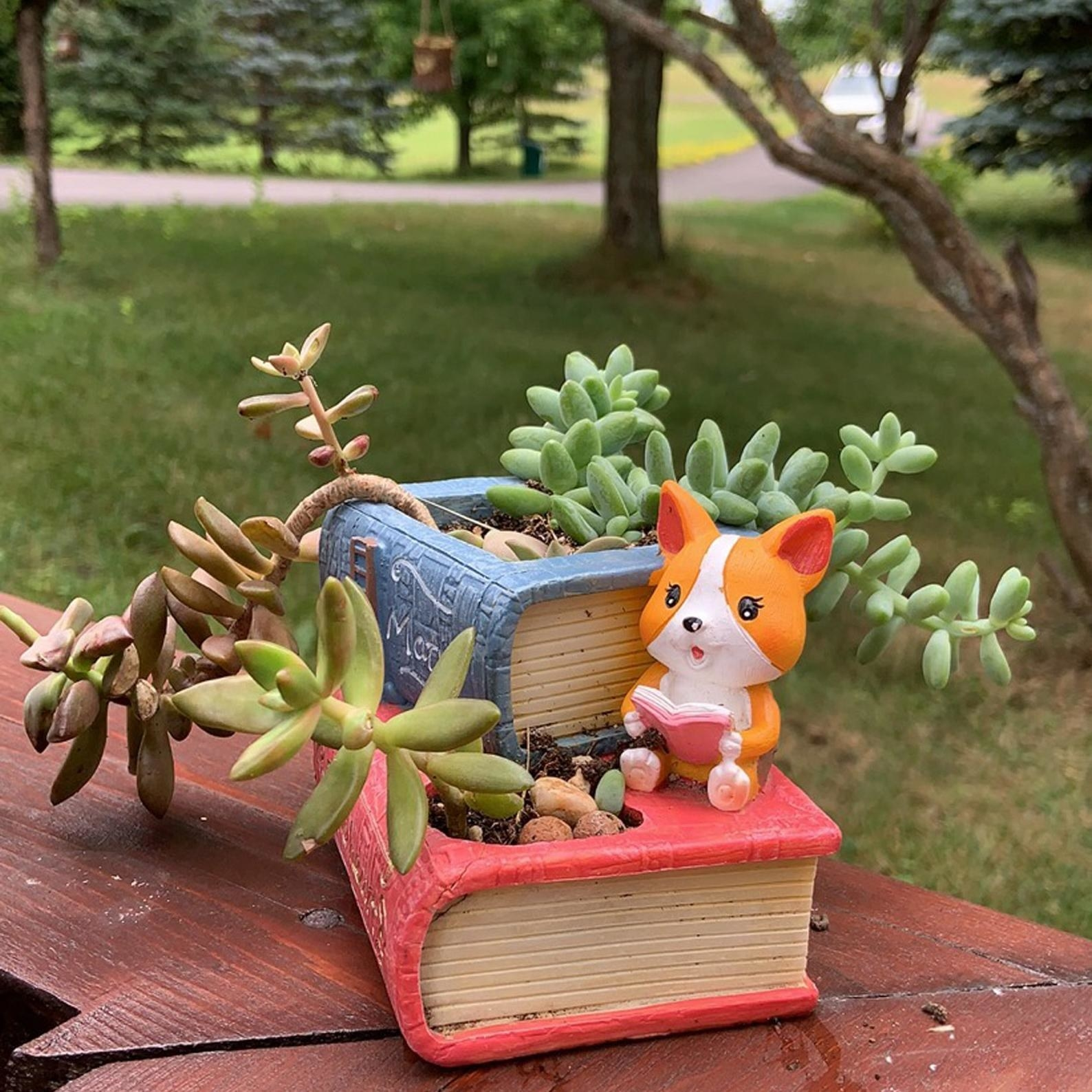 Mini planter of two stacked books with dog reading a book on the side