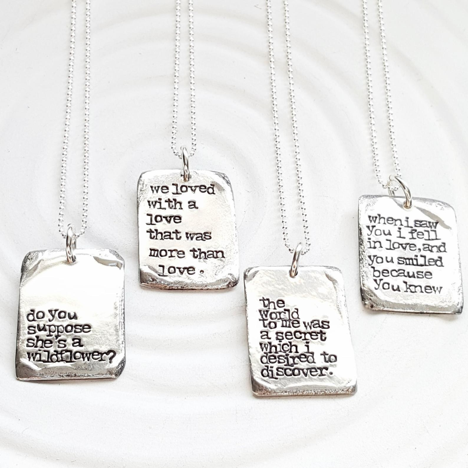 Four pewter pendants with different literary quotes stamped on them