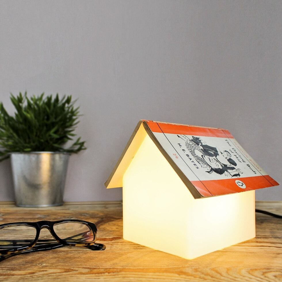 a house-shaped lamp with a book open on top of it