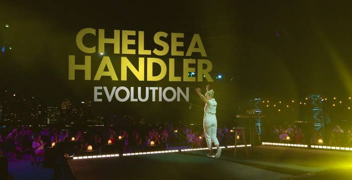 """Chelsea Handler on stage in front of a socially distanced audience with the NYC skyline in the background, and the words """"Chelsea Handler Evolution"""""""