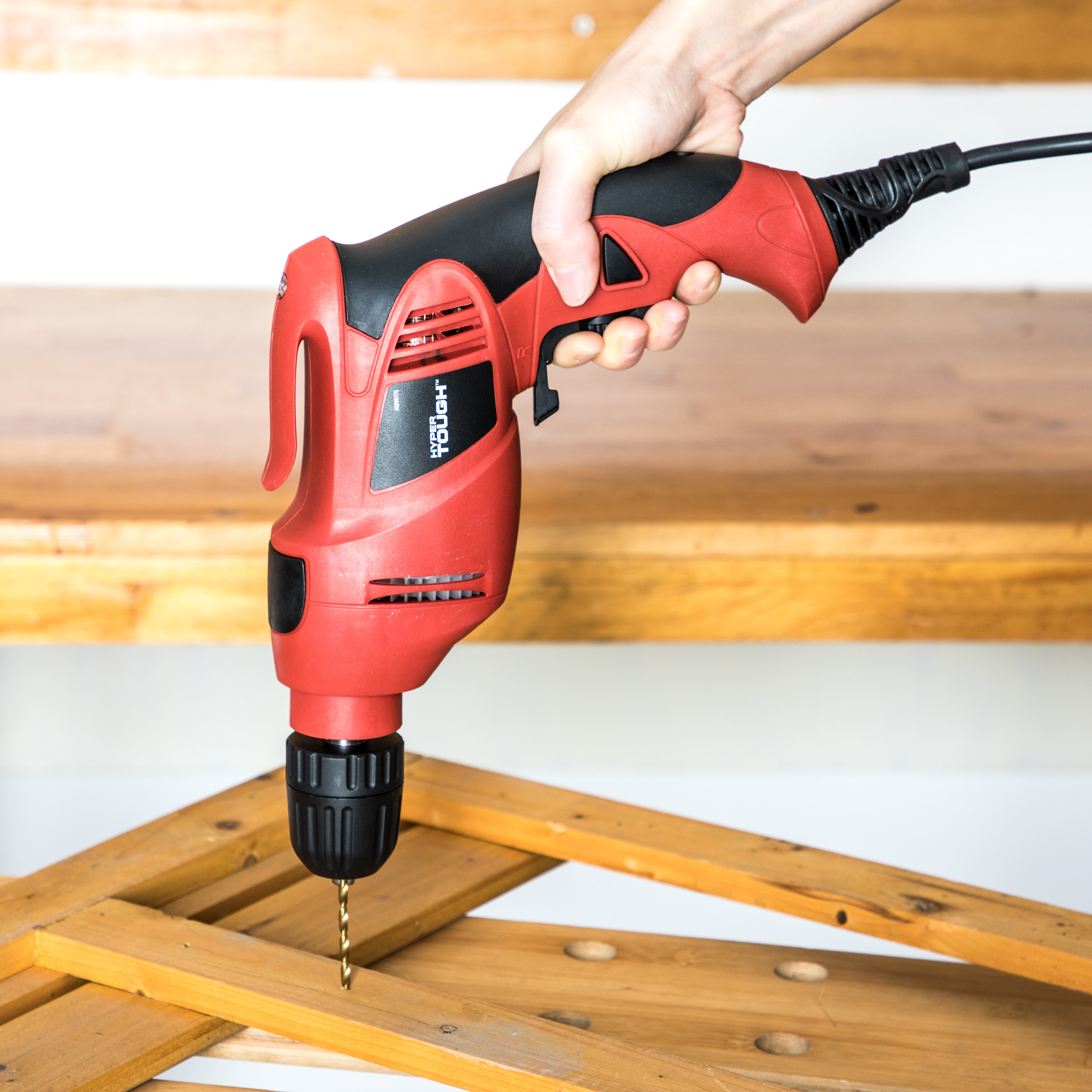 person using a red electric drill to put together a DIY project