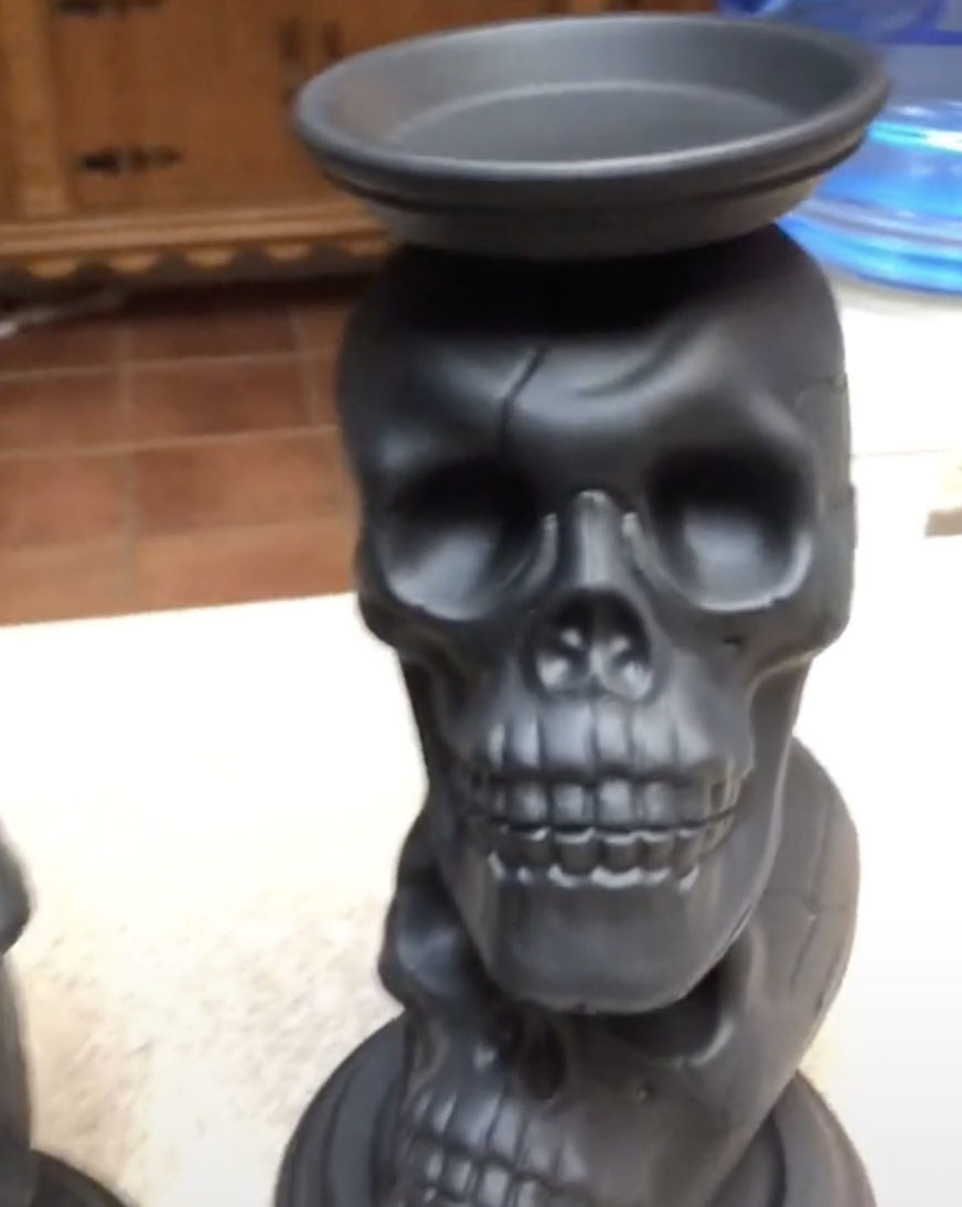A candle holder that is made up of two large black skulls