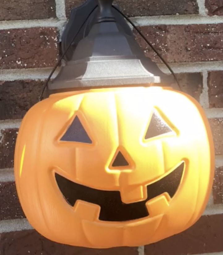 A trick-or-treat candy pail shaped like a pumpkin sits on top of an outdoor light