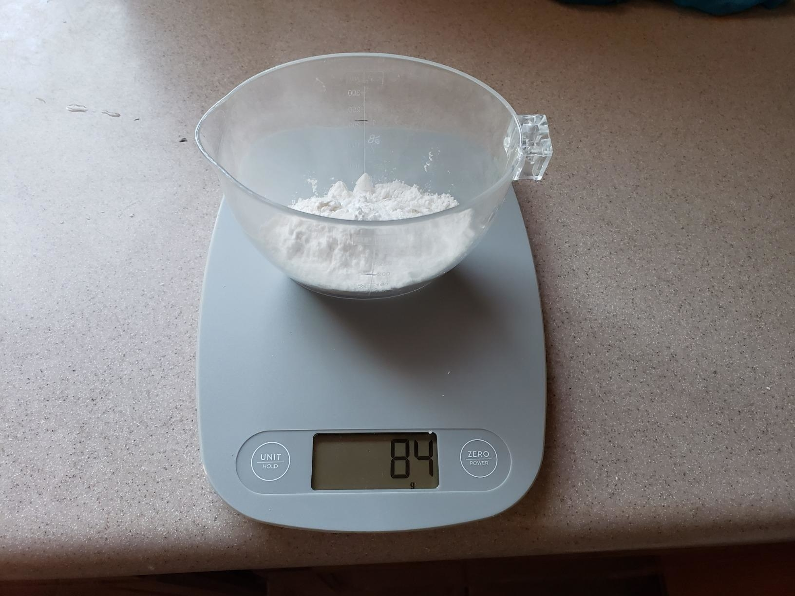 "A cup of flour placed on a gray kitchen scale reading ""8.4"""