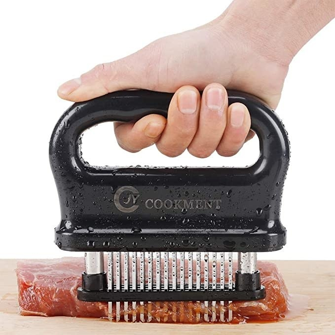 Hand pressing a meat tenderizer into a raw piece of steak.