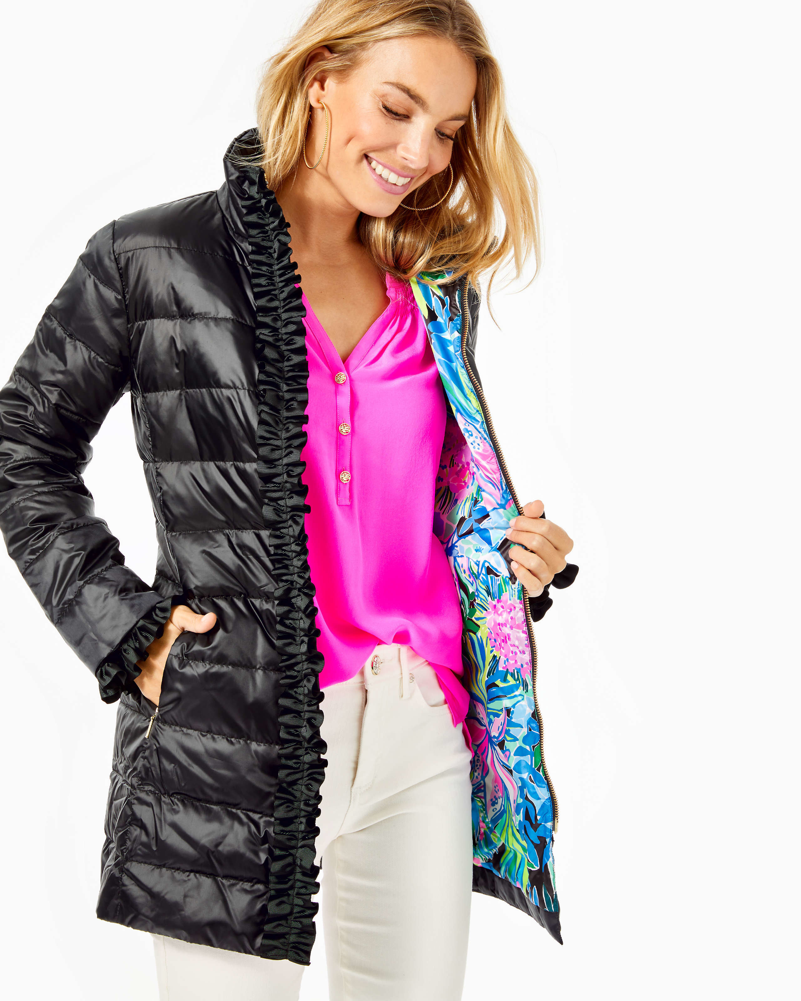 a model in a long black puffer coat with ribbons along the seams and a colorful lilly pulitzer print on the inside