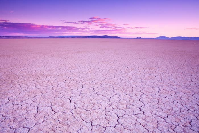 An empty cracked desert landscape with a purple and pink sunset sky