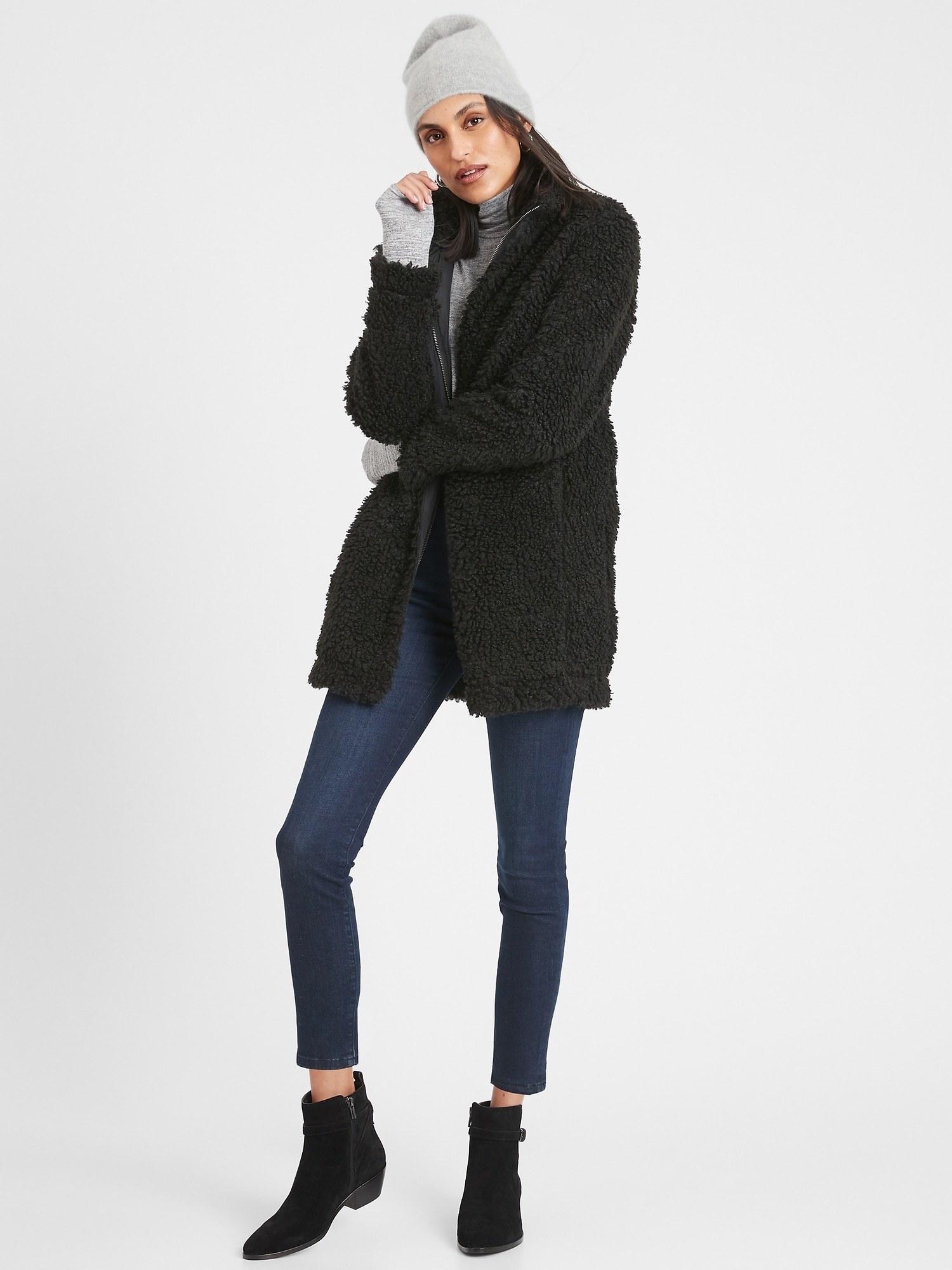 Model in the black hip-length zip-front jacket