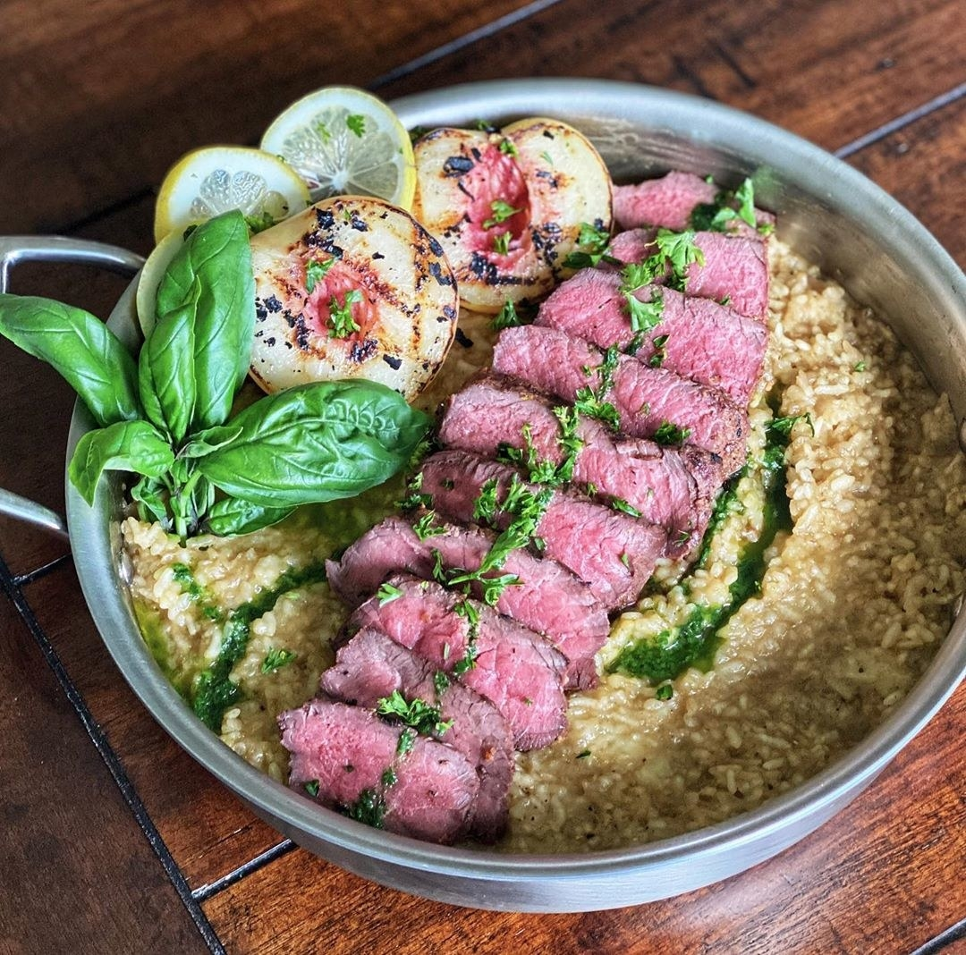 Porter sirloin steak on top of risotto with basil and lemon