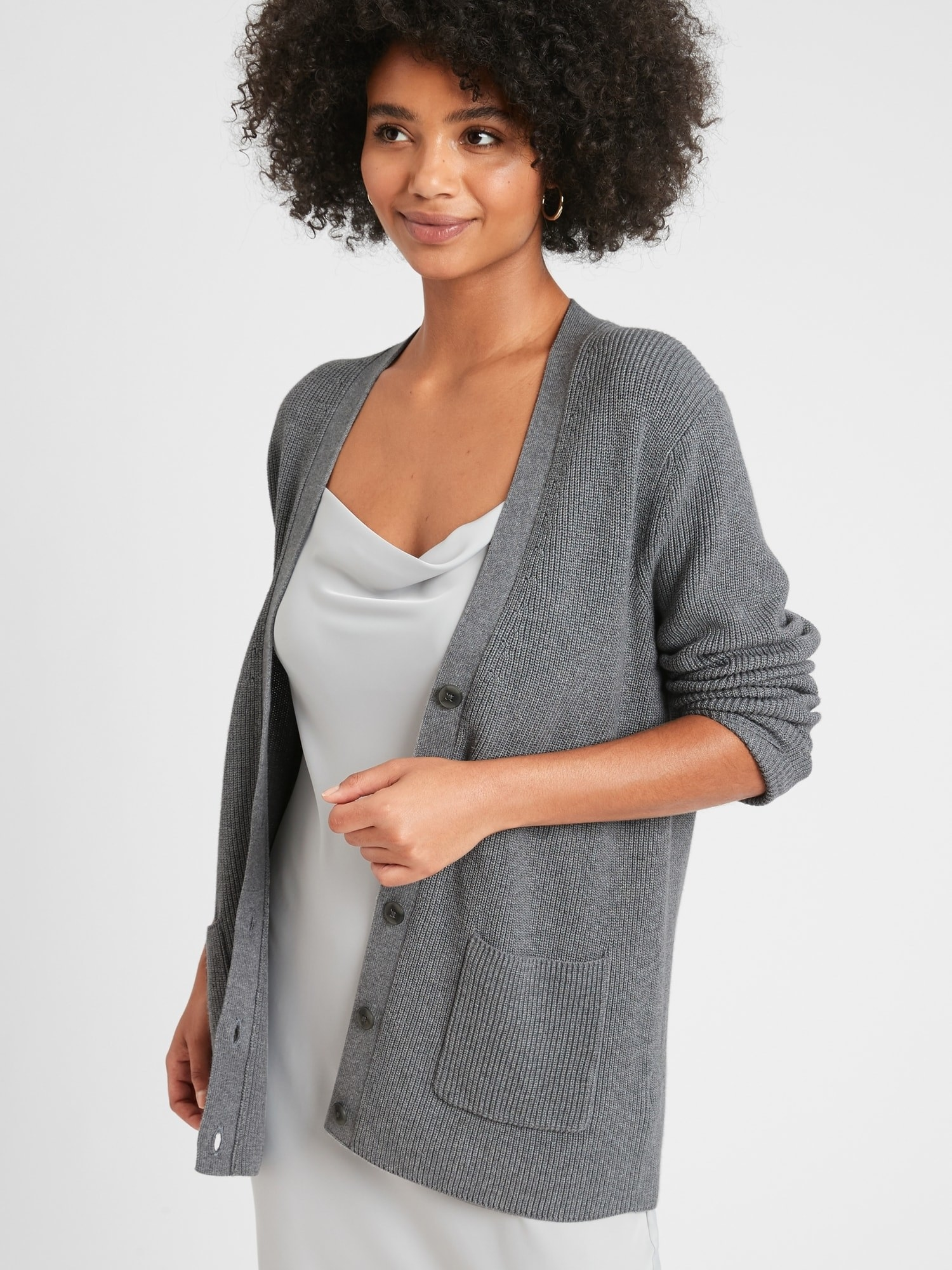 Model in the v-neck cardigan sweater with buttons and a ribbed texture in grey