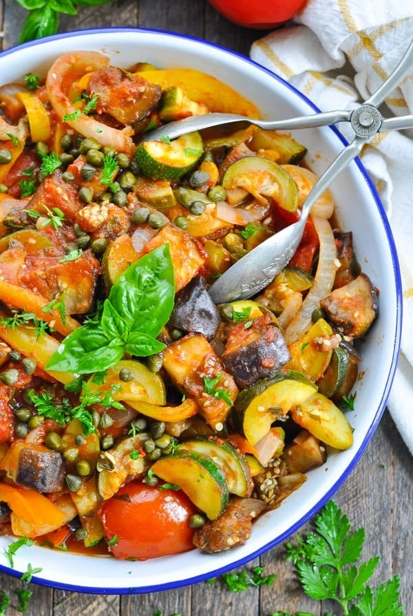 A bowl of ratatouille with eggplant, zucchini, peppers, and capers.