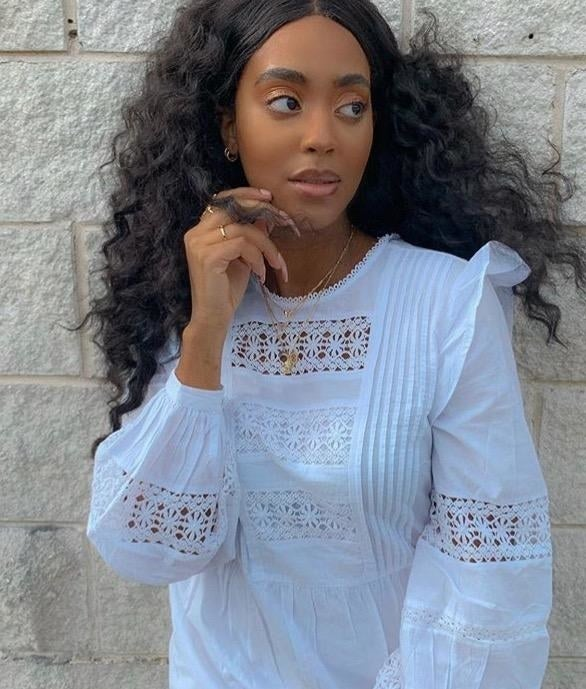 reviewer wearing white high-neck blouse