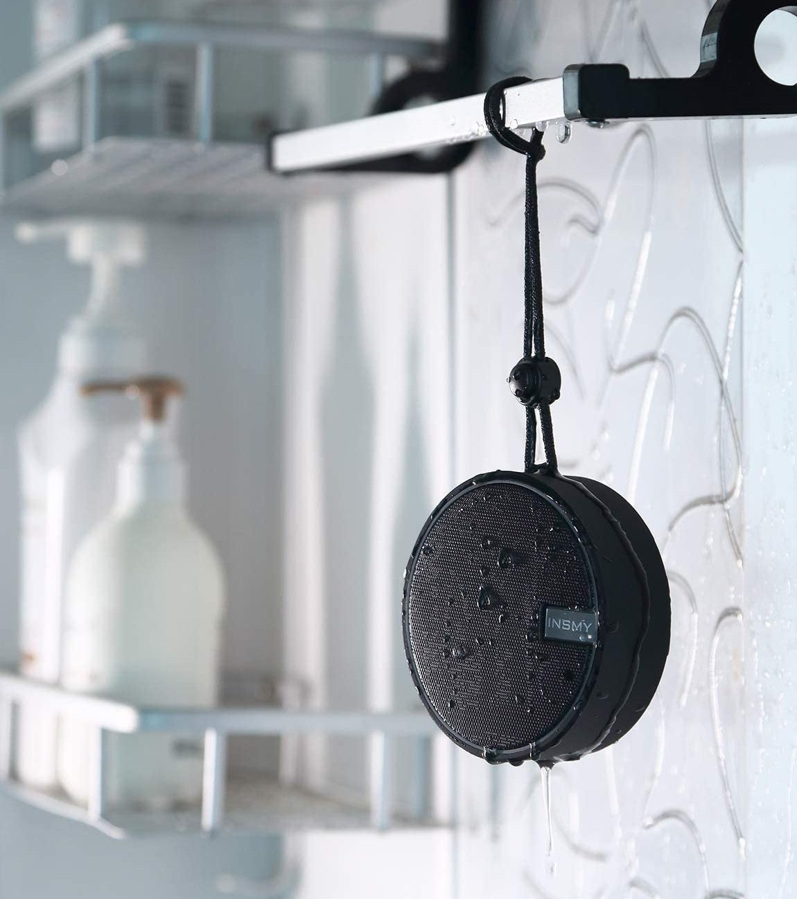 A wet INSMY bluetooth speaker hanging from a bathroom shelf