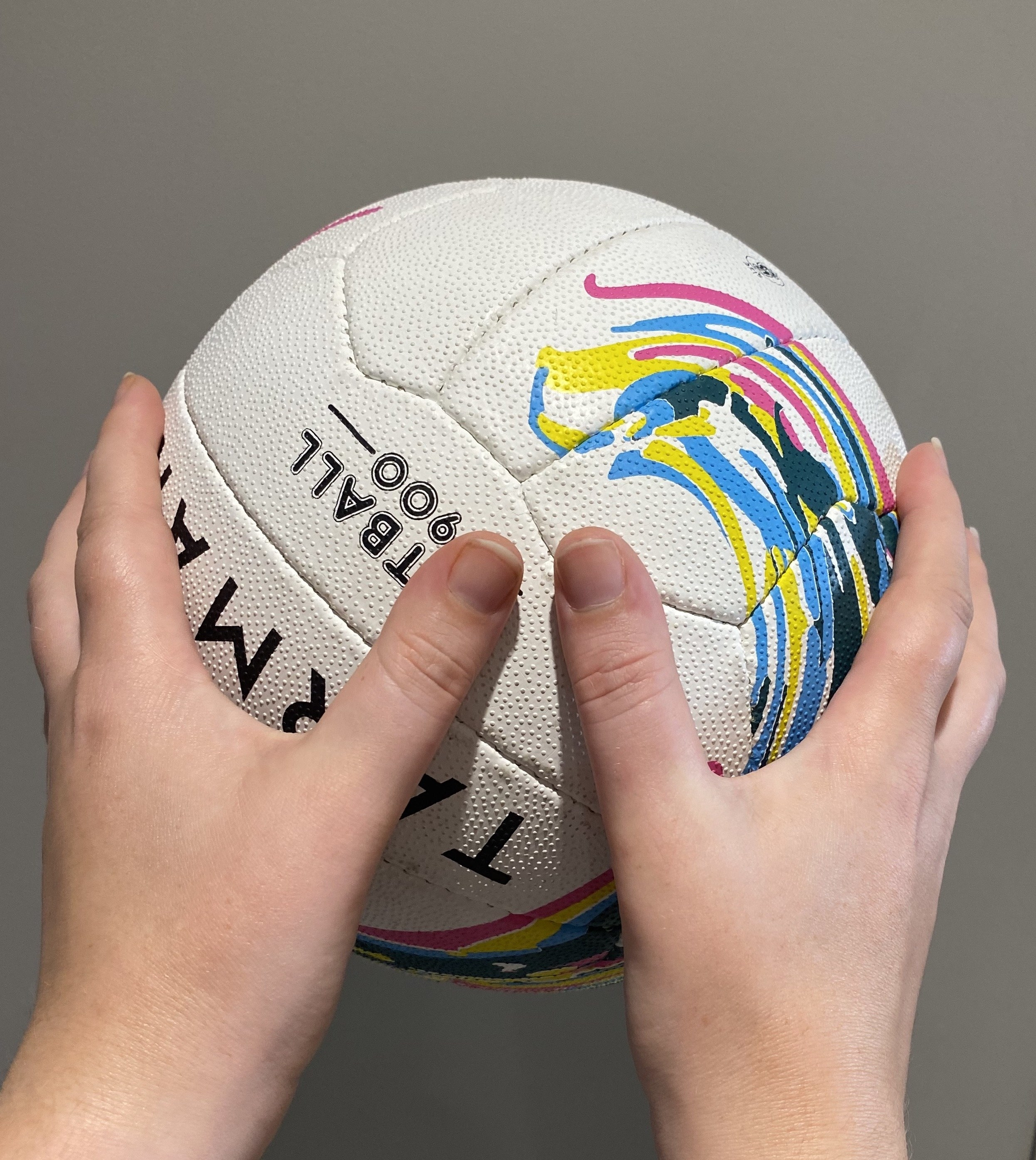 Hands holding a netball with the thumbs close to each other and the fingers splayed around the ball