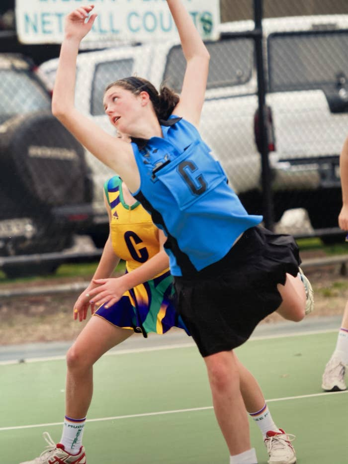 Girl playing centre leans over opponent trying to intercept the ball