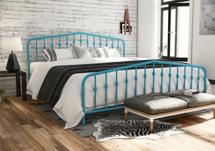 The bed frame, which has a headboard and footboard, each made from slatted colored metal