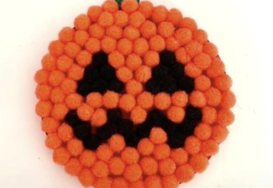 A drink coaster shaped like an orange pumpkin