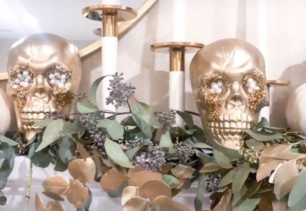 Skulls painted with gold and glitter sit on a mantle