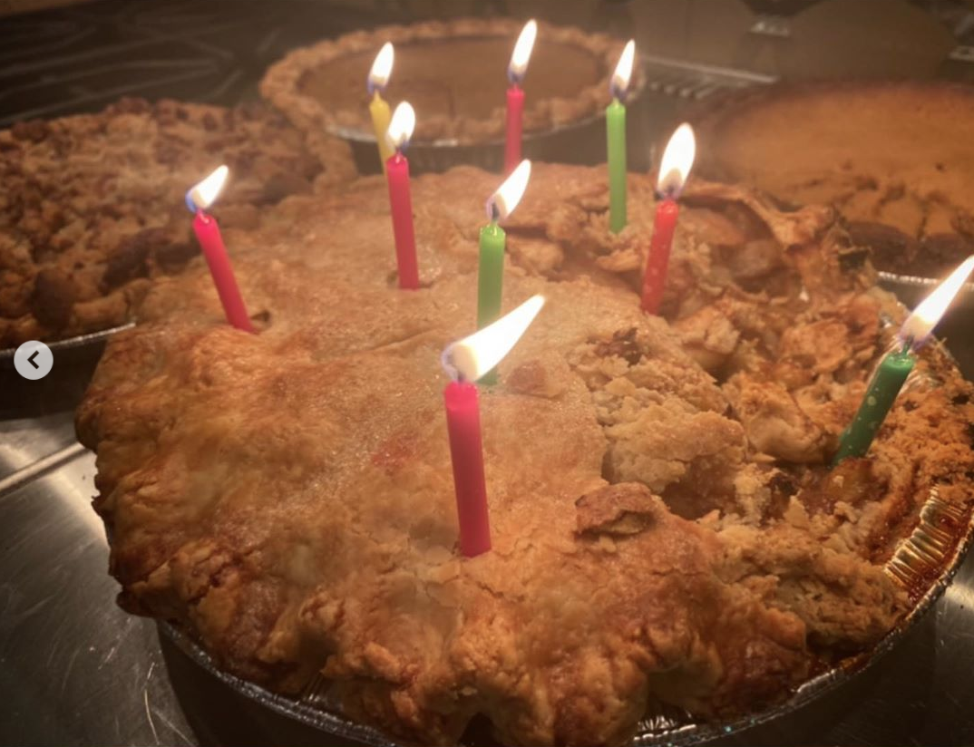 A close up of what looks like homemade apple pie with birthday candles