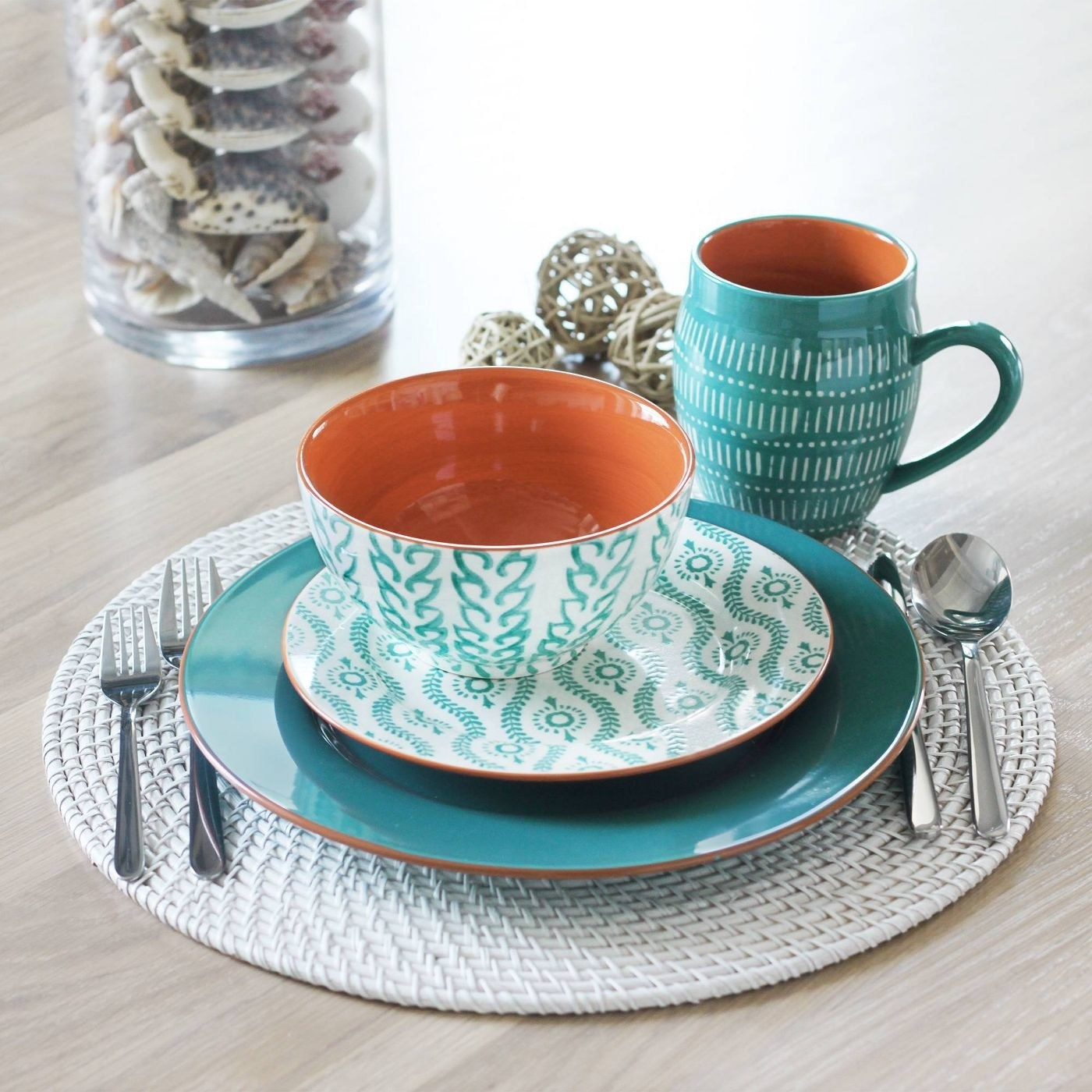 Four pieces of the stoneware dinnerware set on a dining room table