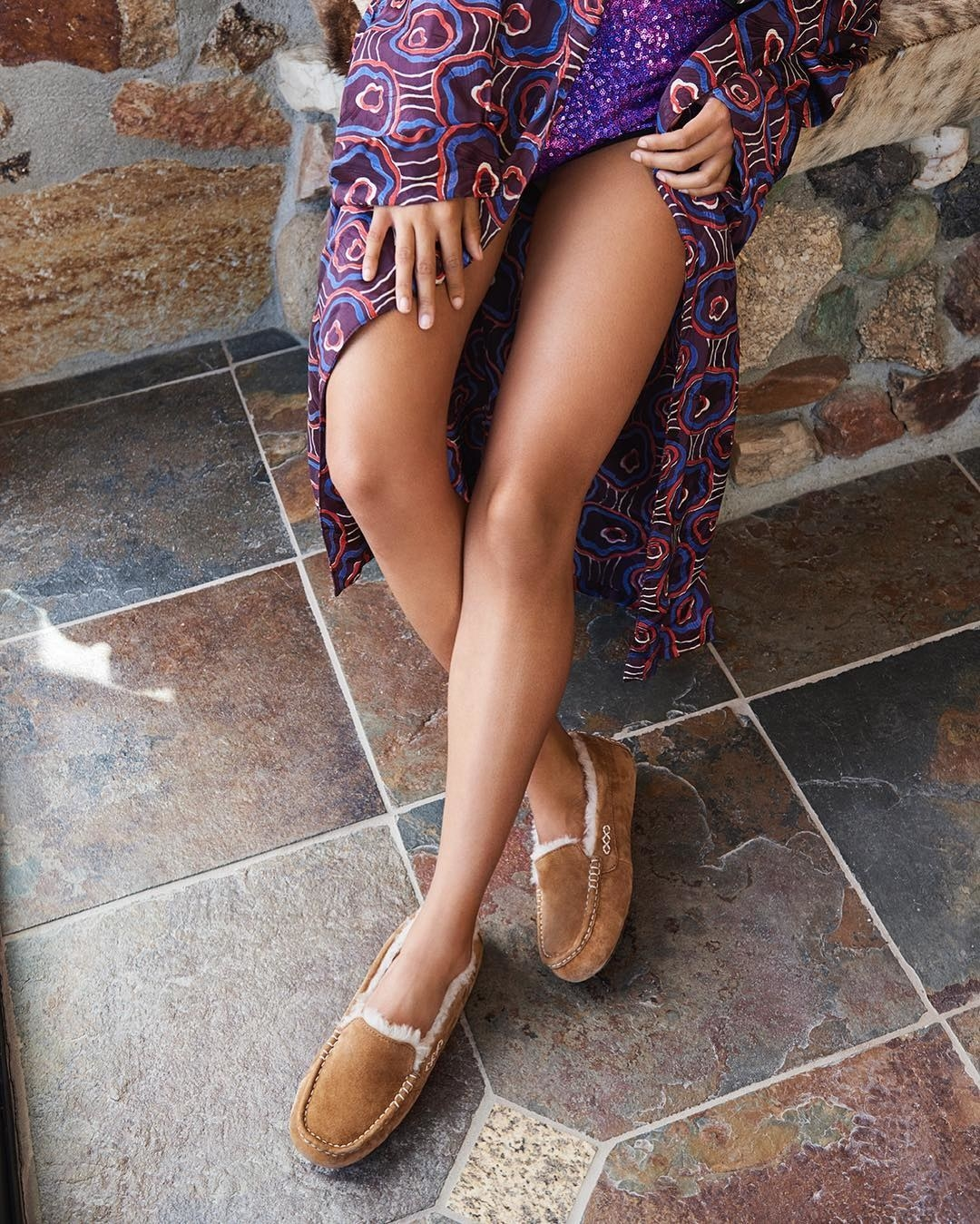 model wearing the brown and white slippers