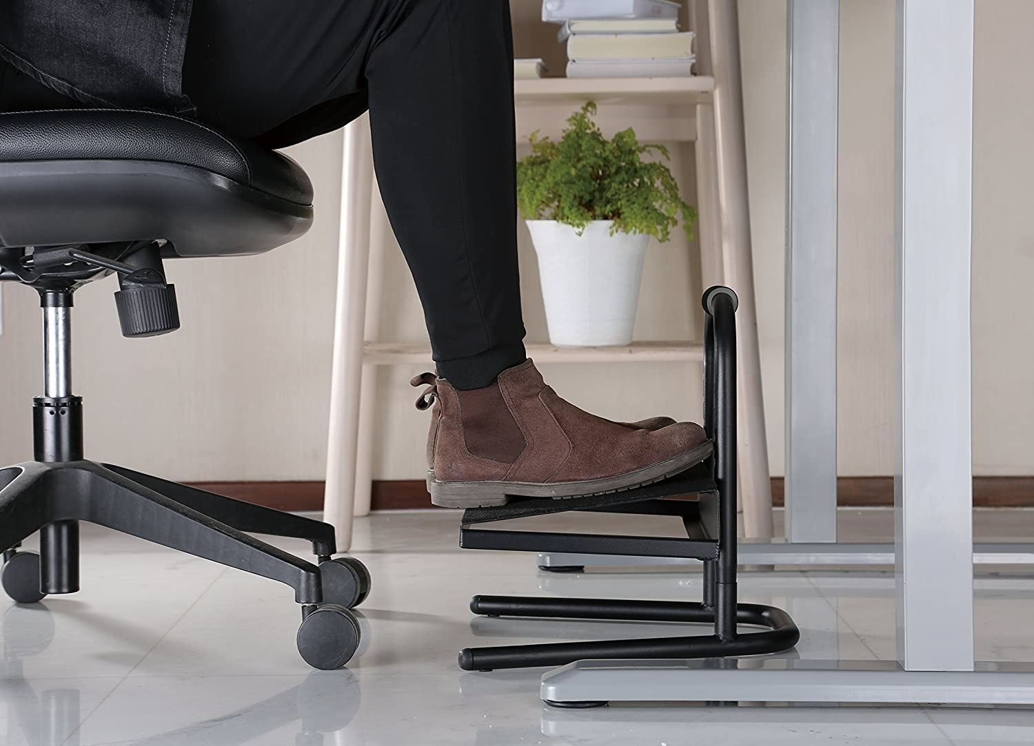 A person's feet on the footrest.
