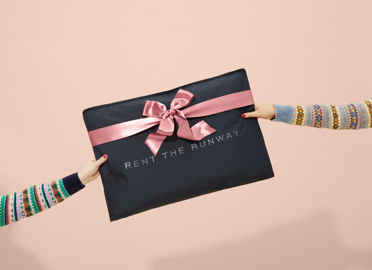 Two arms holding a rent the runway garment bag with a bow on it