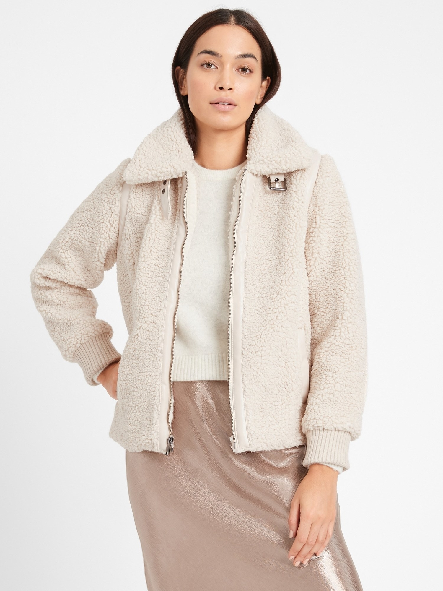 Model in the cream jacket with ribbed cuffs and zip front