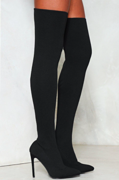 A person wears a pair of thigh-high boots