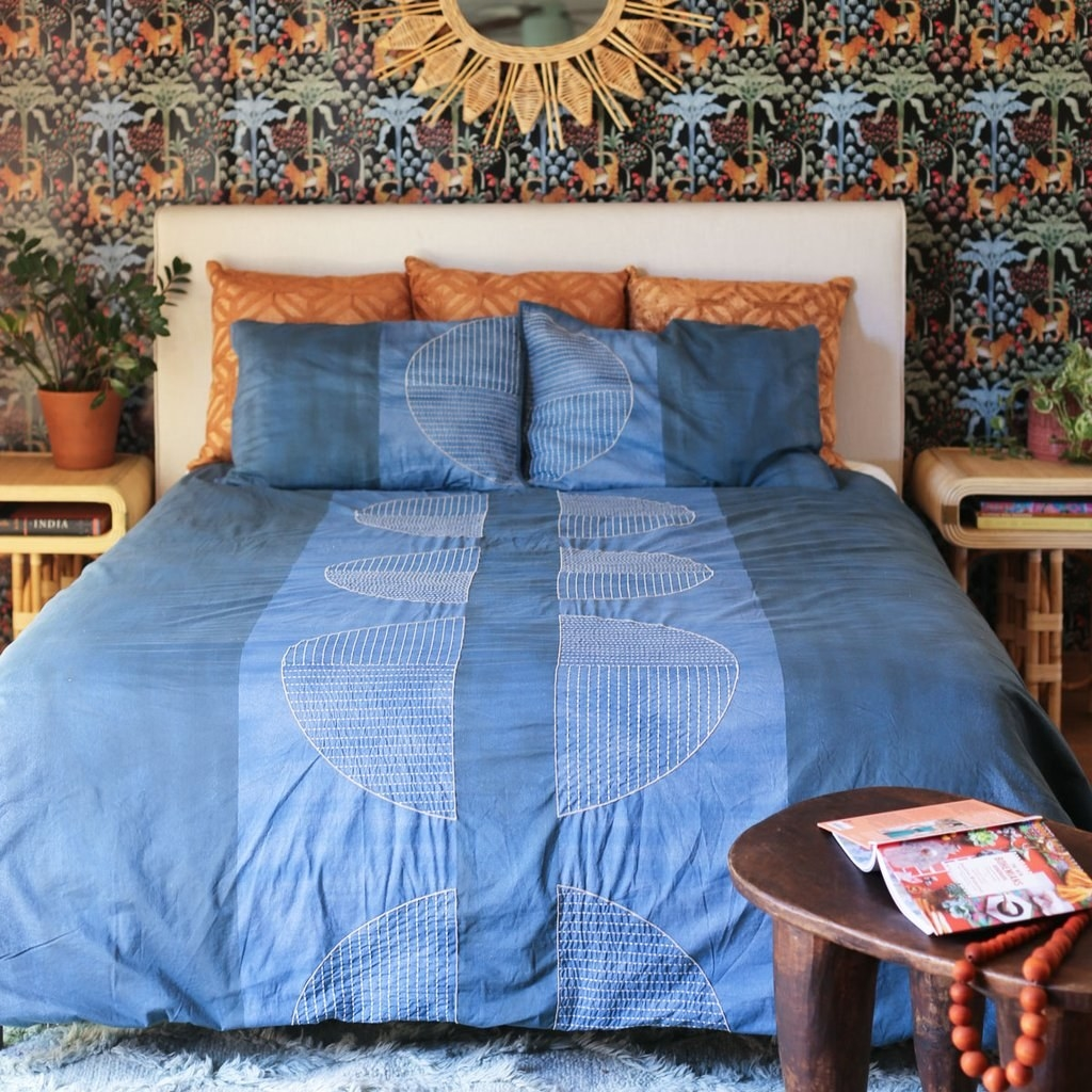 monochromatic blue quilt and shams with a half moon pattern in two stripes down the middle