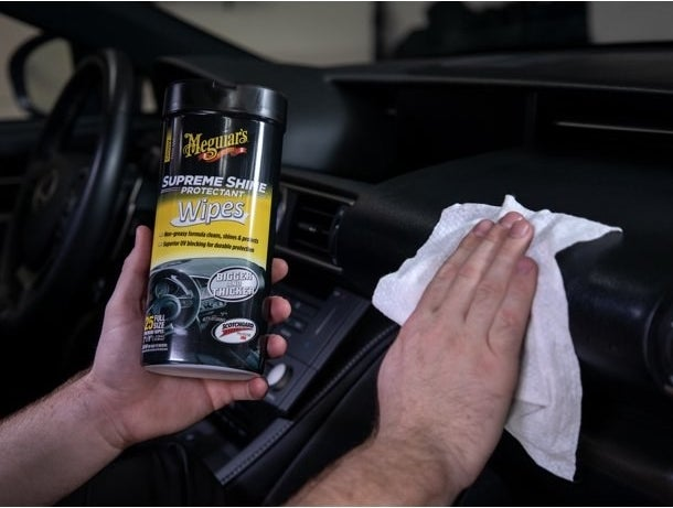 The wipes, which are pre-moistened and paper towel-like, being used to polish a dashboard
