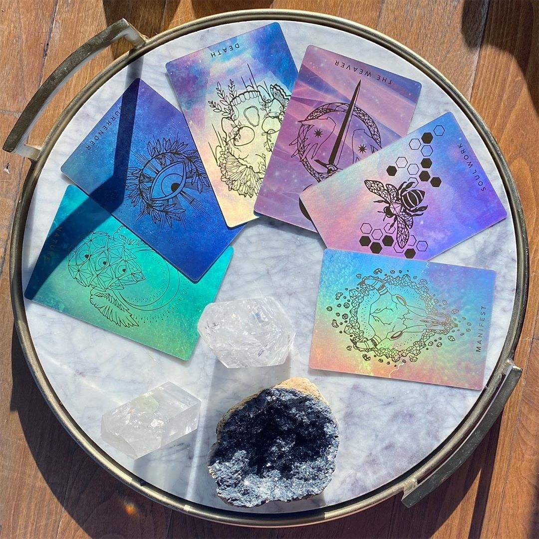 beautiful plastic iridescent cards on a marble platter with crystals