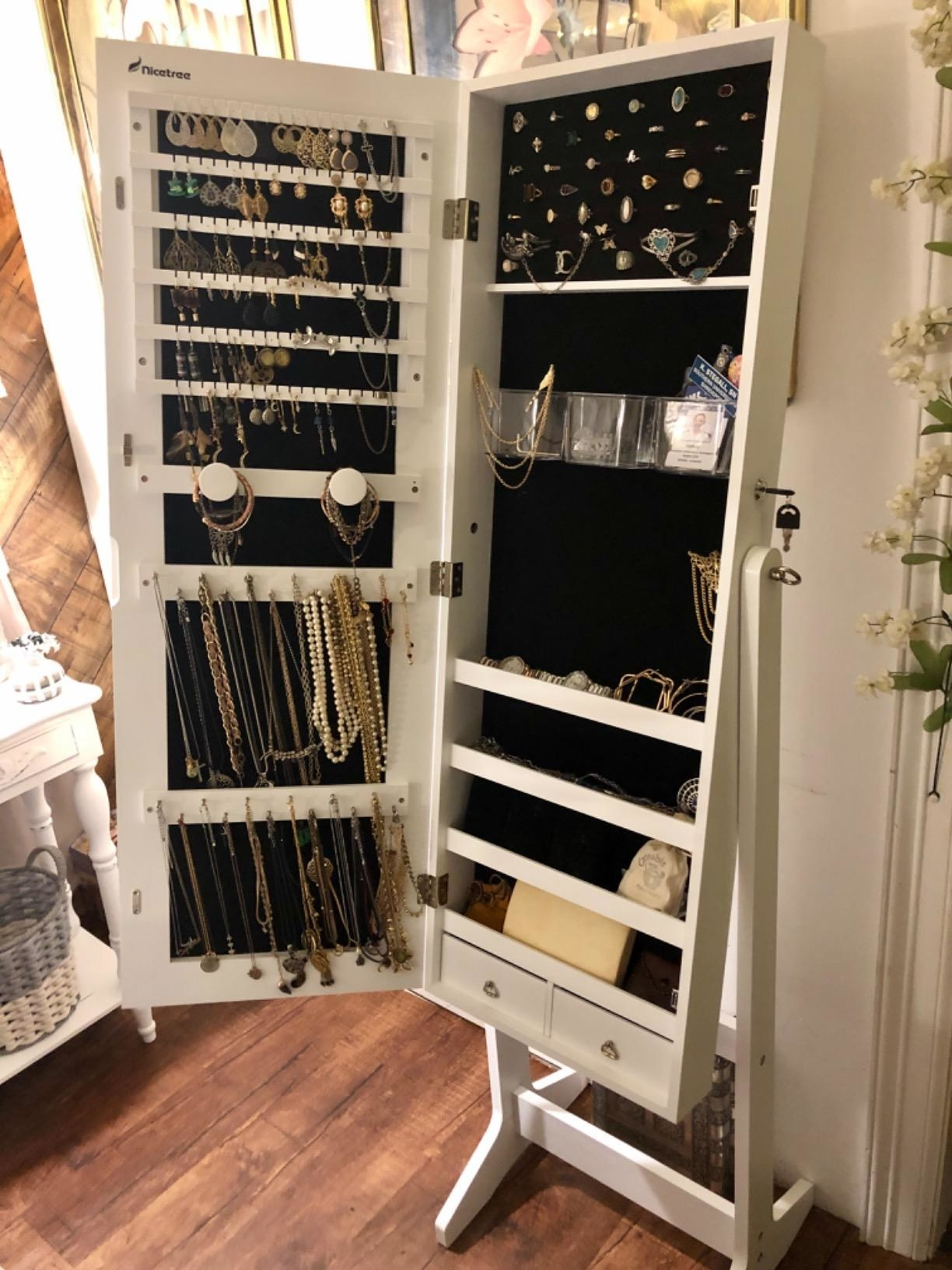 A reviewer showing the mirror rack which opens up to reveal rows of racks for earrings, necklaces, and bracelets and two small drawers on the bottom