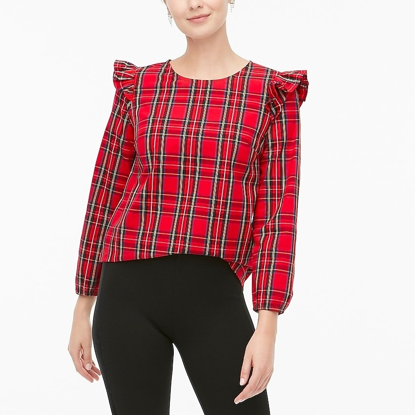 A model wearing the red and black plaid top