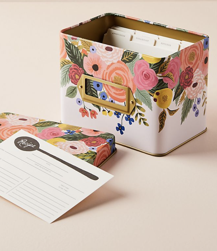 a white tin recipe box covered in pastel florals with the lid off and a single white recipe card lying nearby