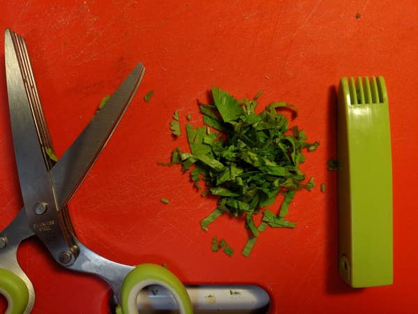 Reviewer's scissors and a pile of cilantro cut using them, plus the cover with the cleaning comb built in