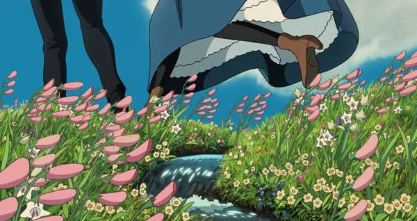 Two sets of feet jump over a small stream in the middle of a field of flowers