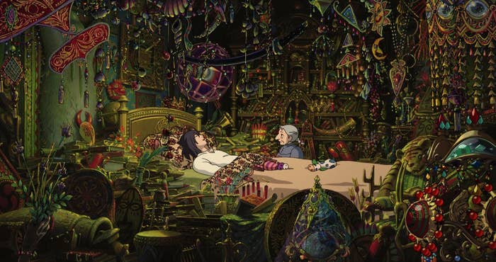 A man in a bed with an old woman sitting next to him, in a room full of sparkling knickknacks