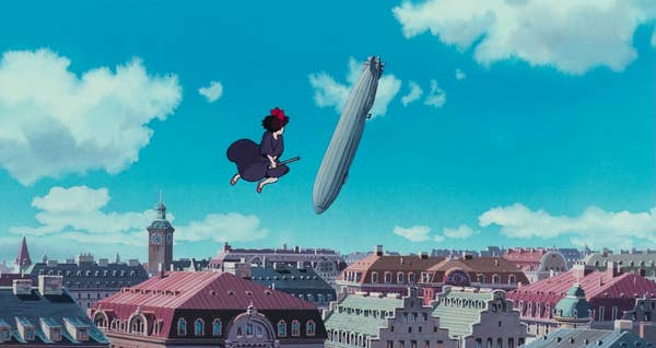 A young girl on a broomstick hovers above a city with a blimp falling from the sky in the background